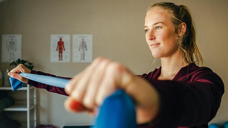 Eine jüngere Frau trainiert im Stehen mit einem Fitnessband.