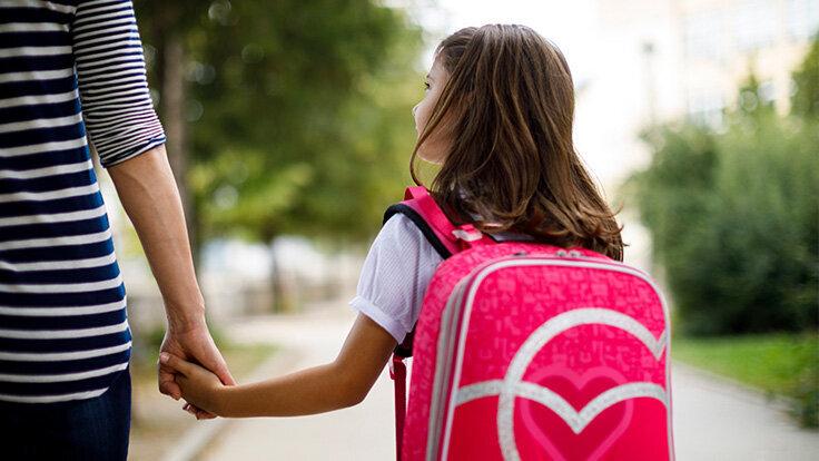 Eine Mutter bringt ihre Tochter mit pinken Schulranzen auf dem Rücken zur Schule.