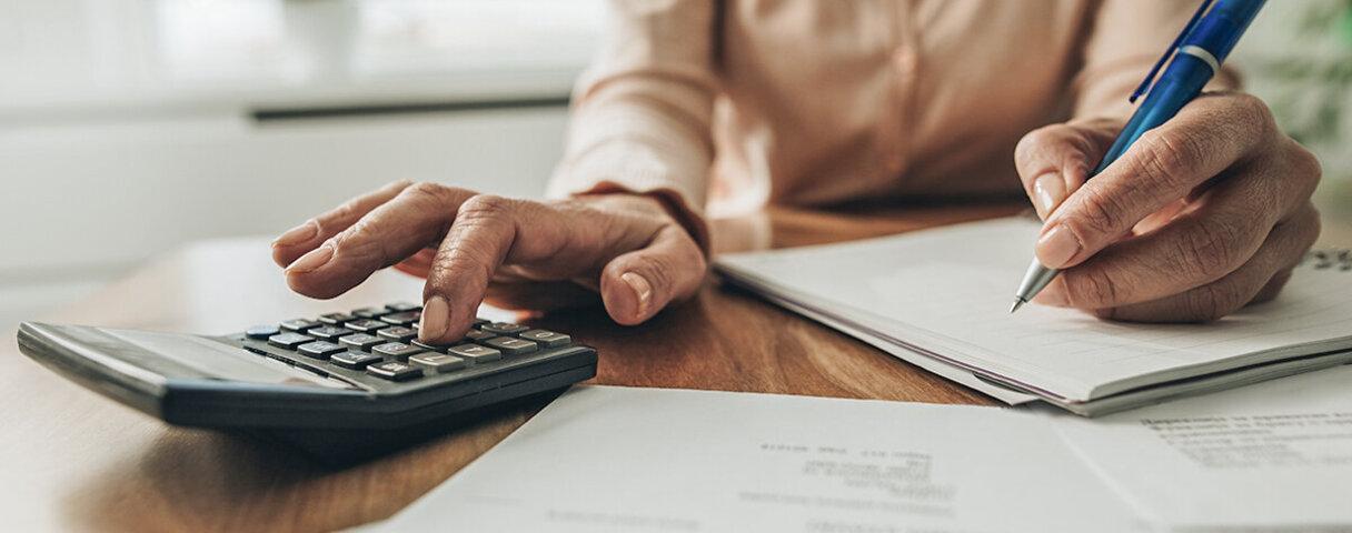 Mann ist geizig und berechnet akribisch seine Ausgaben mit dem Taschenrechner.
