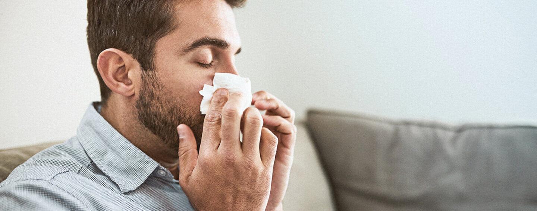 Ein Mann schnäubt sich die Nase wegen einer Hausstaubmilbenallergie.