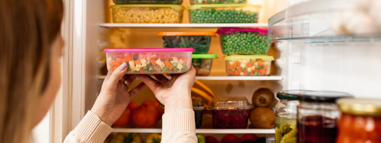 Frau möchte Lebensmittel frisch halten und verstaut sie im Kühlschrank.
