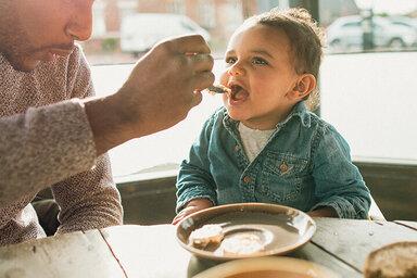 Vater reicht seinem Baby Essen und versucht so, es an feste Nahrung zu gewöhnen