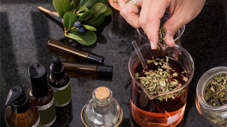 Naturmedizin- Heilkräuter werden in ein Glas gefüllt.