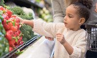 Kleines Mädchen darf beim kauf von Gemüse helfen und greift zur roten Paprika.