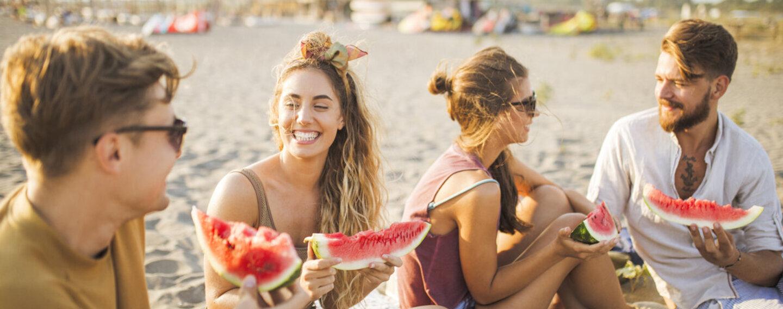 Lachende Menschen am Strand mit Wassermelone