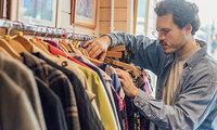 Mann schaut in einem Geschäft durch einen Kleiderständer.