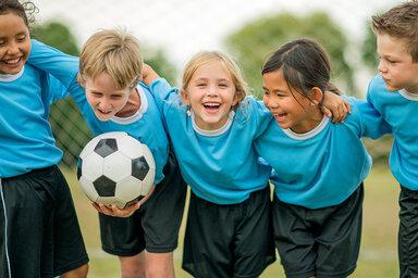 Fünf Fußball spielende Kinder umarmen sich und lachen.