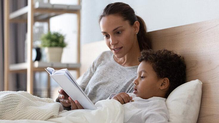Entspannungstechniken: Mutter liest Kind zur Entspannung vor.