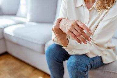Frau leidet durch ihre Fibromyalgie unter schmerzen Gelenken und massiert ihre Hand.