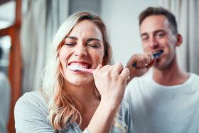 Ein junges Paar putzt sich vor dem Badezimmerspiegel die Zähne.