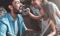 Gesunde Ernährung für Kinder: Mutter, Vater und Tochter bereiten gemeinsam einen Salat zu.