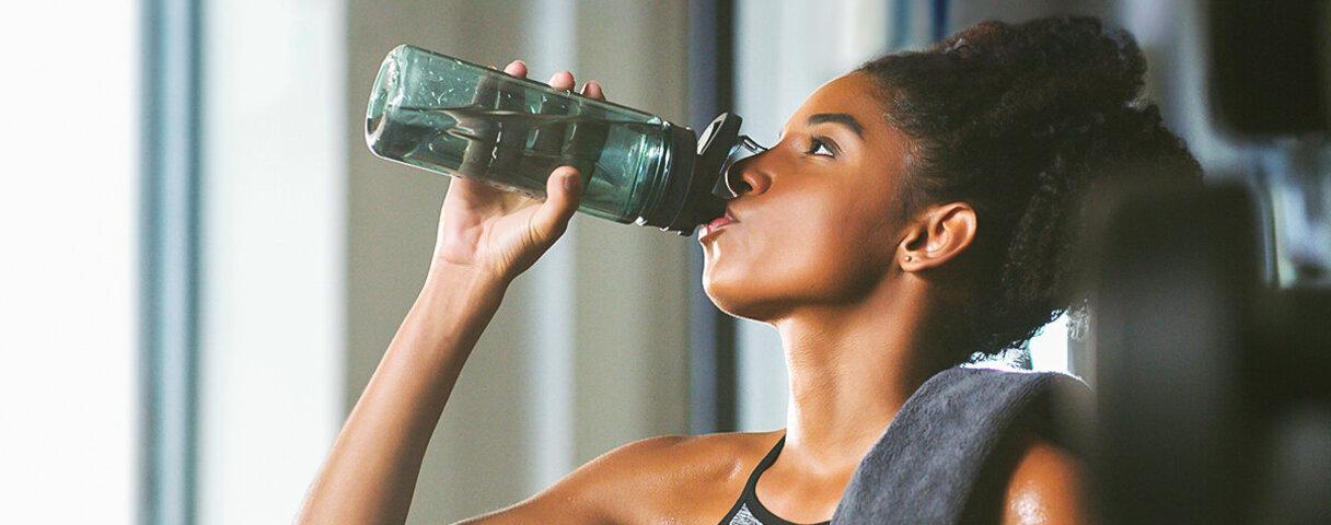 Eine Frau trinkt Wasser aus einer Flasche aus, denn sie weiß, dass man viel trinken muss.