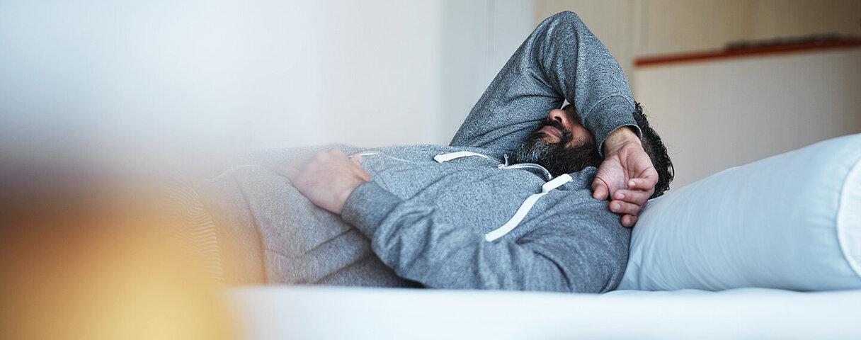 Mann mit psychosomatischen Beschwerden liegt auf der Couch.