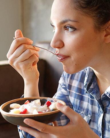 Junge Frau isst Obstsalat und damit garantiert glutenfrei.