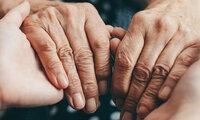 Zwei Personen halten sich an den Händen. Sie halten zusammen, denn jemand ist schwerkrank – Umgang mit dem Tod.