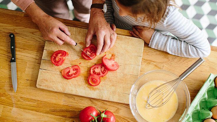 Großmutter und Enkelkind bereiten zusammen Abendbrot vor, sie schneiden Tomaten auf einem Brett.