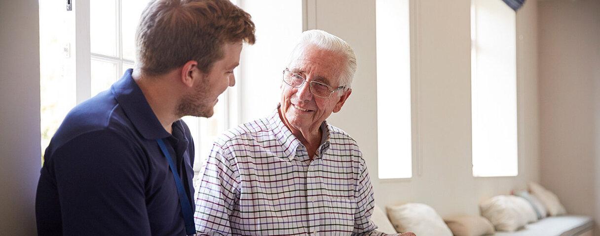 Ein junger Mann schaut sich mit einem dem Demenzpatienten ein Fotoalbum an.