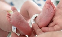 Neugeborenes wird an den Füßen gehalten