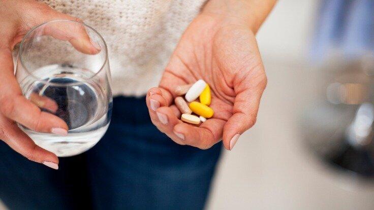 Eine Frau hält ein Glas Wasser und Vitaminpräparate in der Hand.