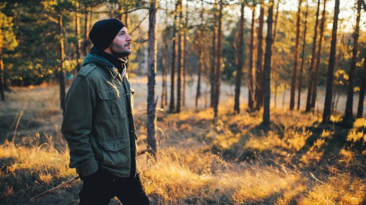 Ein Mann geht im Wald spazieren, um Magenschmerzen loszuwerden.