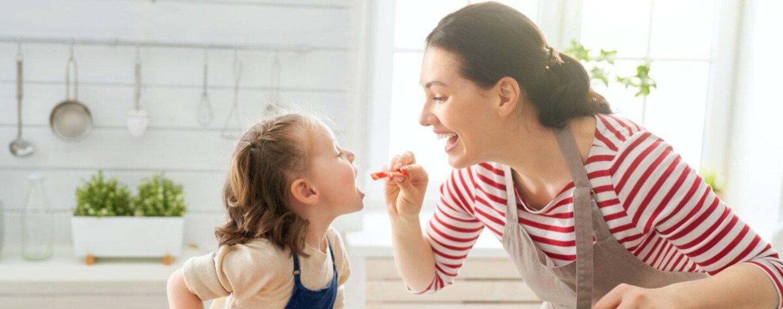 Gesunde Ernährung: Eine Mutter hält ein Stück Tomate in der Hand und gibt sie ihrem Kind.