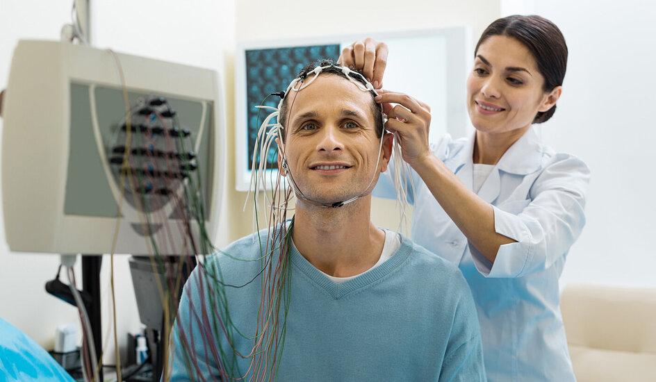 Eine Ärztin des Schlaflabors befestigt Elektroden am Kopf eines Patienten.