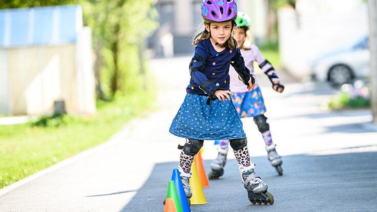 Kinder üben das Inlineskaten mit Parkour und Schutzausrüstung.