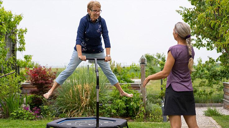 Ältere Frau macht Jumping Fitness auf einem Trampolin unter Anleitung einer Trainerin.