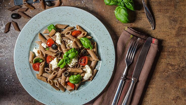 Auf einem Teller sind Vollkornnudeln mit Tomaten, Oliven, Mozzarella und Basilikum serviert.
