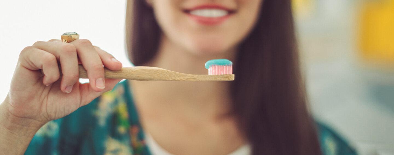 Frau legt Wert auf nachhaltige Zahnpflege und greift zur Bambus-Zahnbürste.