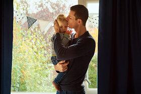 Ein Vater hält sein Baby auf dem Arm und tröstet es.