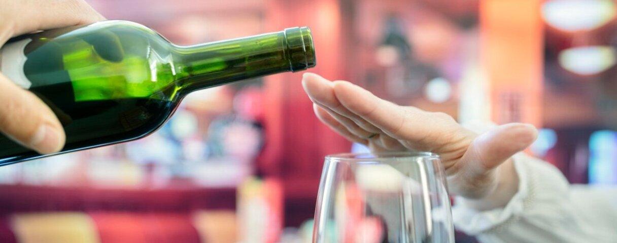 Frau macht Alkoholverzicht und schlägt einen Rotwein aus.