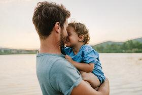 Ein Vater hält sein kleines Kind auf dem Arm. Durch Nähe und Zuwendung können Kinder Resilienz entwickeln und stärken.