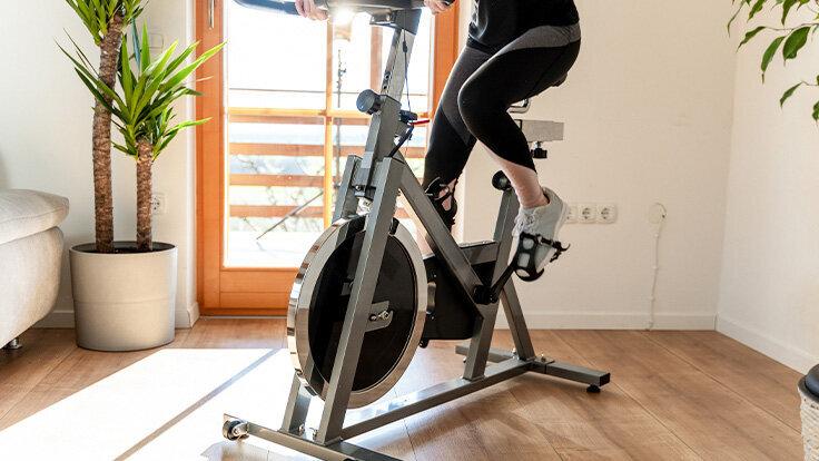 Eine junge Frau trainiert auf einem Spinning-Bike in ihrem Wohnzimmer