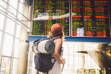Frau schaut auf eine Anzeige am Flughafen, sie ist alleine auf einer Reise unterwegs.