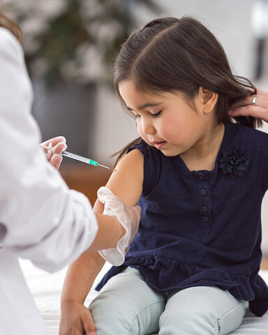 Ein Arzt verabreicht einem Mädchen eine Impfung, in Anwesenheit der Mutter.