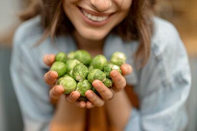 Eine Frau hält beide Hände voll Rosenkohl, welcher den ganzen Herbst über Saison hat.