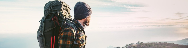 Ein Backpacking-Tourist genießt auf einem Berggipfel die Aussicht