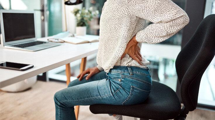 Haltung, Frau stützt ihren schmerzenden Rücken.