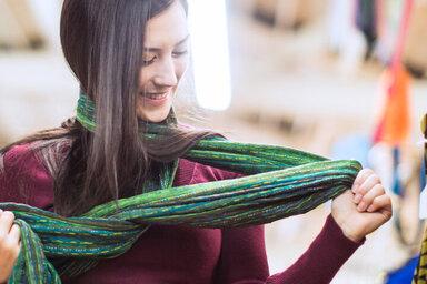 Eine Frau begutachtet ihr recyceltes Kleidungsstück.