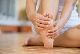 Eine Frau sitzt auf dem Boden und massiert sich die Füße.