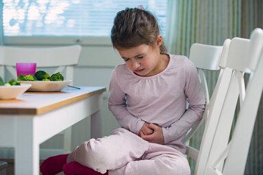 Ein Mädchen sitzt am Küchentisch und hält sich mit schmerzverzerrtem Gesicht den Bauch – vielleicht steckt eine Lebensmittelallergie dahinter.