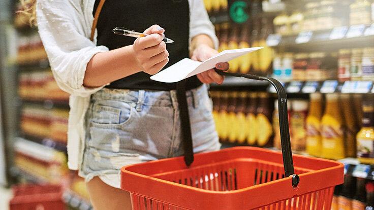Eine Frau geht im Supermarkt ihren Einkaufszettel durch.