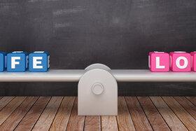 """Eine ausgeglichene Waage, auf der Würfen mit der Aufschrift """"Life"""" und """"Love"""" stehen."""