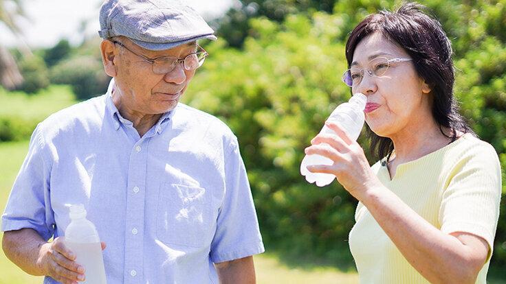 Ein älteres Paar trinkt im Park Wasser, um sich vor Überhitzung zu schützen.