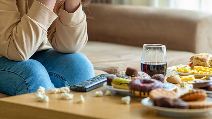 Frau mit Binge Eating ist verzweifelt, weil sie nicht aufhören kann zu essen.