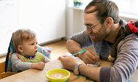 Ein Vater füttert sein Kind mit dem ersten Babybrei.