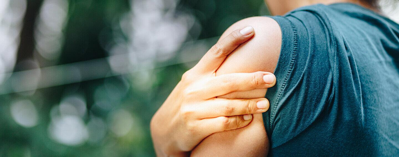 Eine junge Frau fasst sich an ihre schmerzende Schulter.