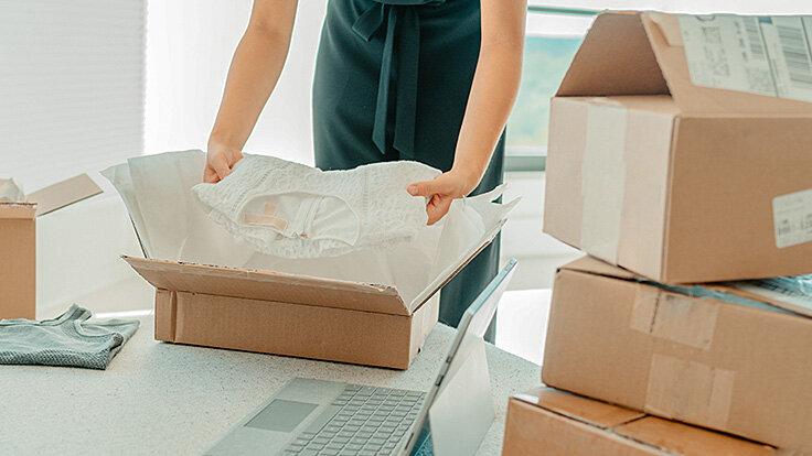 Mehrere Pakete vom Online-Shopping sind im Raum verteilt, eins wird gerade von einer Person ausgepackt