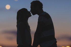 Silhouette eines sich küssenden Paares vor dem unscharfen Hintergrund eines Stadtpanoramas.